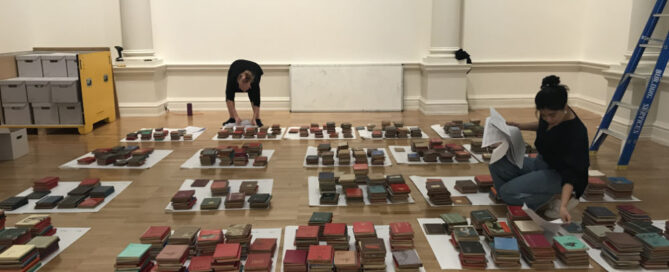 Conservators working on floor surrounded by stacks of books